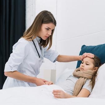 Ernstige vrouwelijke arts die de temperatuur van een meisje controleert dat op bed met koorts ligt
