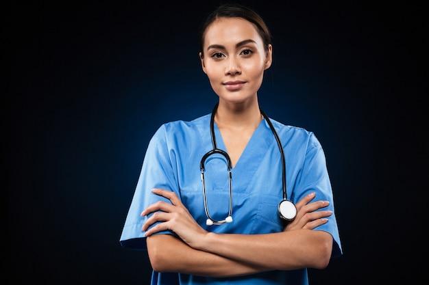 Ernstige vrouwelijke arts die en gevouwen handen kijkt houdt