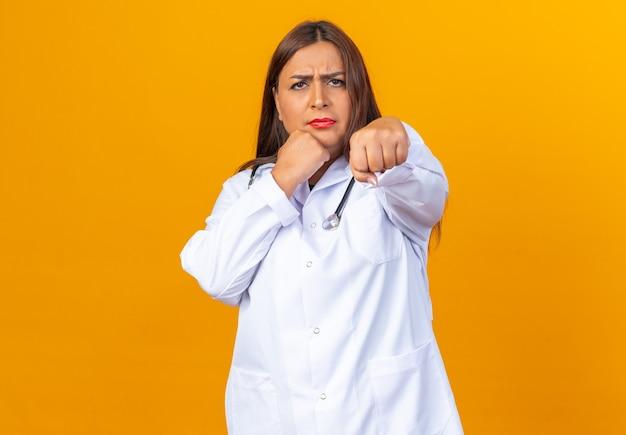 Ernstige vrouwelijke arts van middelbare leeftijd in witte jas met stethoscoop die zich voordeed als een bokser met gebalde vuist