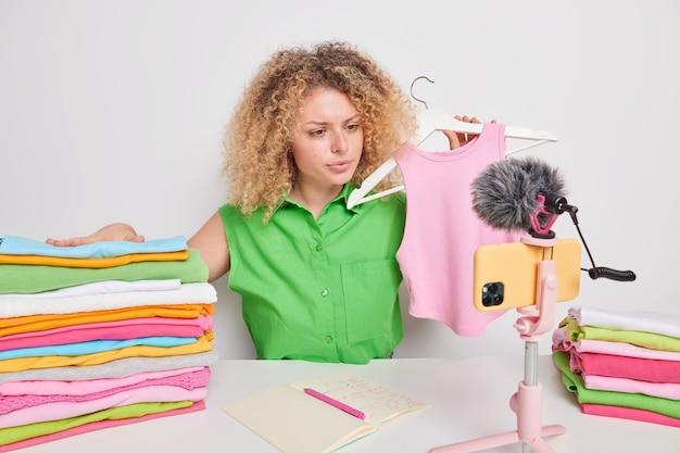 Ernstige vrouwelijke blogger die betrokken is bij aankoop op afstand aandelen nieuwe merkkleding houdt roze shirt op hanger records livestream video poseert rond netjes opgevouwen wasgoed verkoopt outfit via e-winkel