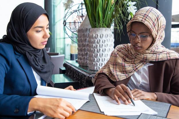 Ernstige vrouwelijke collega's die documenten in koffie bestuderen