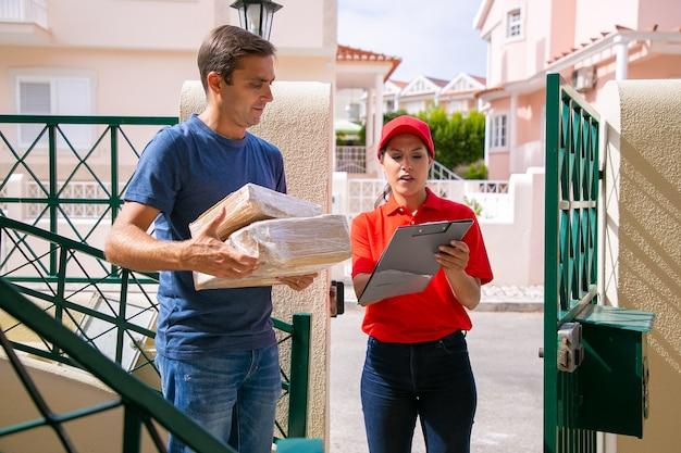 Ernstige vrouwelijke koerier in rood glb die adres aan cliënt toont en klembord houdt. nadenkende man bestelling ontvangen en permanent met pakketten in handen. bezorgservice en online winkelconcept