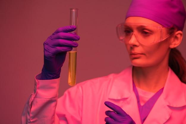 Ernstige vrouwelijke laboratoriumtechnicus in handschoenen die lange reageerbuis gevuld met urine houden tijdens het doen van analyse