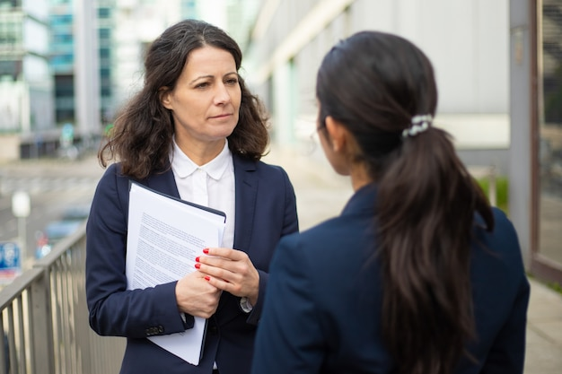 Ernstige vrouwelijke ondernemers praten op straat
