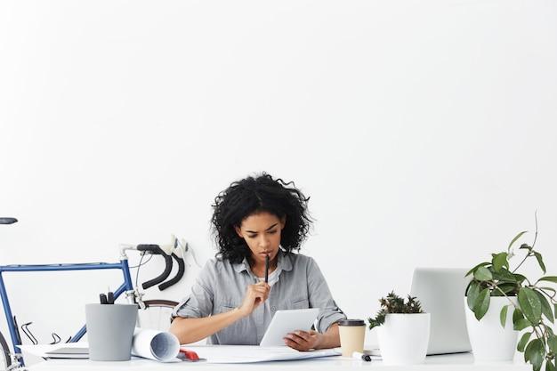 Ernstige vrouwelijke ontwerper die haar interieur op digitale tablet controleert