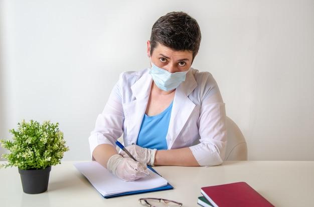 Ernstige vrouwelijke therapeut met beschermend masker schrijft diagnose op, zittend aan bureau tegenover patiënt