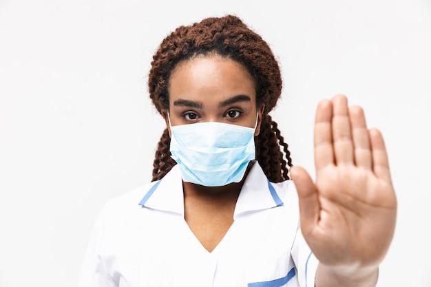 Ernstige vrouwelijke verpleegster die een medisch gezichtsmasker draagt dat een stopgebaar toont met de hand geïsoleerd tegen een witte muur