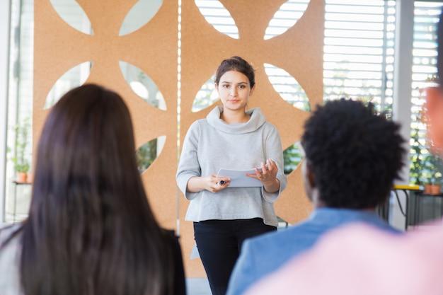 Ernstige vrouwelijke vrouw die project voorstelt aan klasgenoten