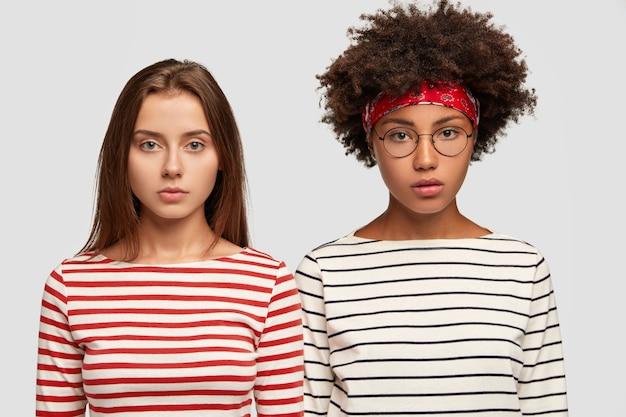 Ernstige vrouwelijke zusters van gemengd ras gekleed in gestreepte truien, kijken serieus