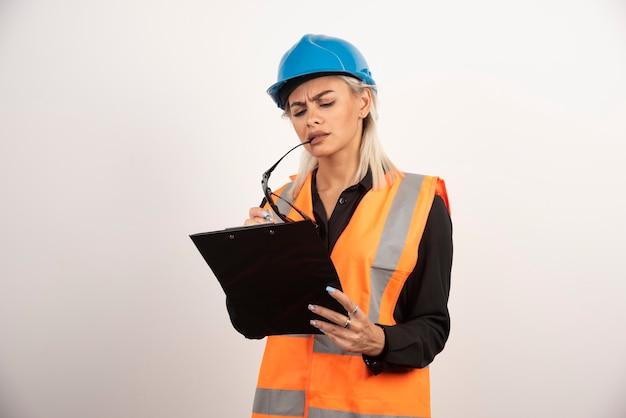 Ernstige vrouwenbouwer die met helm op klembord kijkt. hoge kwaliteit foto