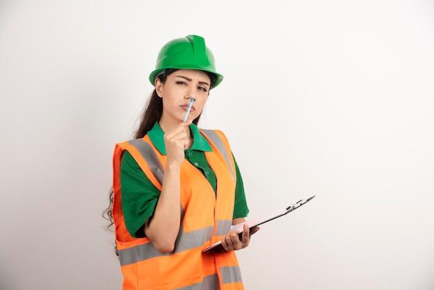 Ernstige vrouweningenieur met klembord op witte achtergrond. hoge kwaliteit foto