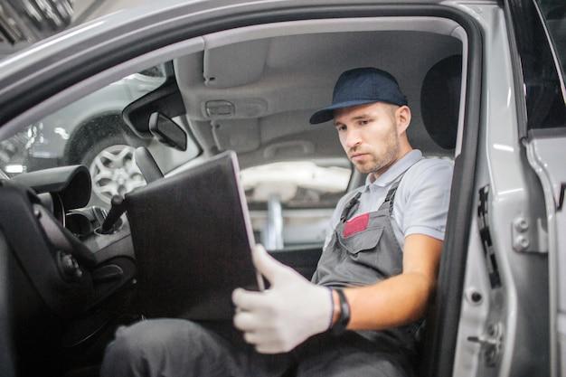 Ernstige werknemer zit in de auto en houdt laptop. hij houdt het vast met handen in handschoenen. guy werkt eraan. hij maakt computerdiagnose voor auto.