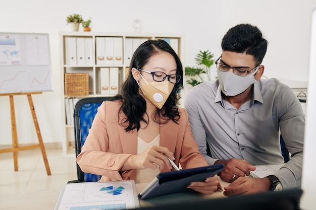 Ernstige zakencollega's met beschermende maskers die aan een bureau aan een bureau zitten en een grafiek op het scherm van een digitale tablet bespreken
