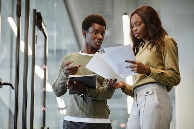 Ernstige zakencollega's staan in de kantoorgang en bespreken het verkooprapport dat ze voorbereiden op...