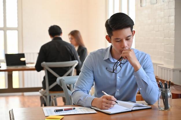 Ernstige zakenman die aan lijst in coworking ruimte werkt