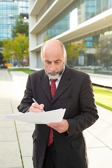 Ernstige zakenman die nota's over straat neemt