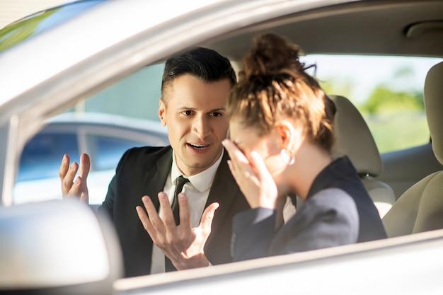 Ernstige zakenman en huilende vrouw in een auto