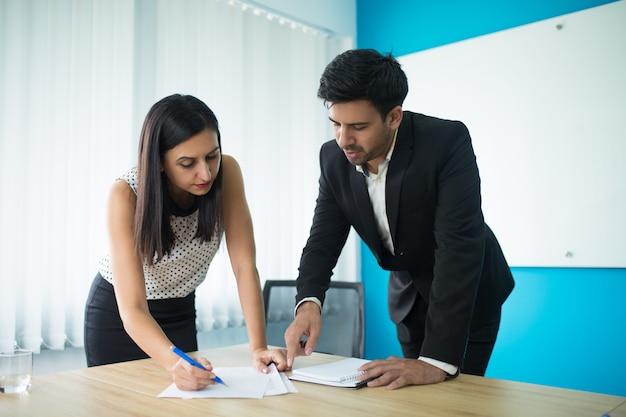Ernstige zakenman en onderneemster die contract ondertekenen