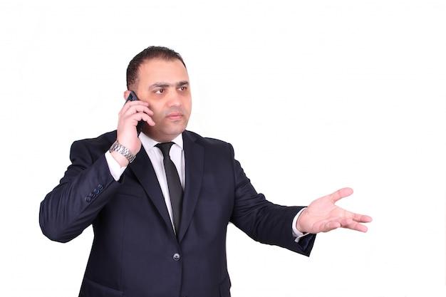 Ernstige zakenman in een pak en stropdas ruzie door de telefoon. bedrijfsconcept geïsoleerd
