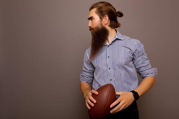 Ernstige zakenman in formele slijtage met rugbybal die op grijze achtergrond wordt geïsoleerd