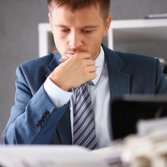 Ernstige zakenman in het kantoor onderzoekt documenten