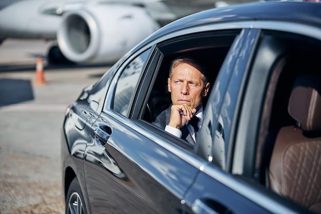 Ernstige zakenman in pak gaat met de auto op de achterbank nadat hij met het vliegtuig naar het vliegveld is gevlogen