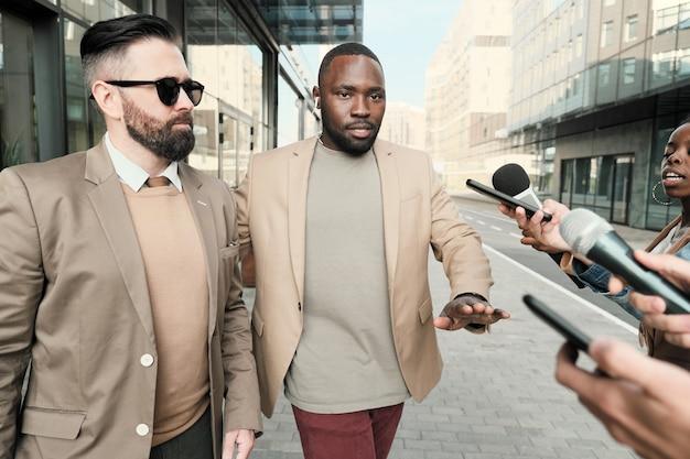 Ernstige zakenman in zonnebril met zijn lijfwacht die een interview geeft aan journalisten in de stad