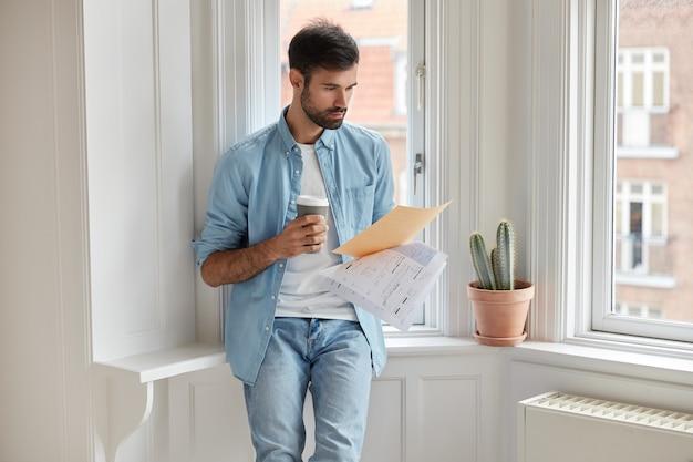 Ernstige zakenman leest contracttekst, analyseert documentatie, concentreerde zich op financiële informatie