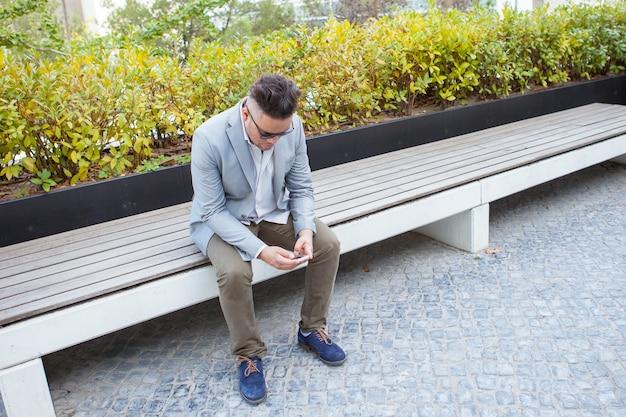Ernstige zakenman met behulp van smartphone in park