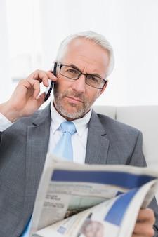Ernstige zakenman met cellphone en krant thuis