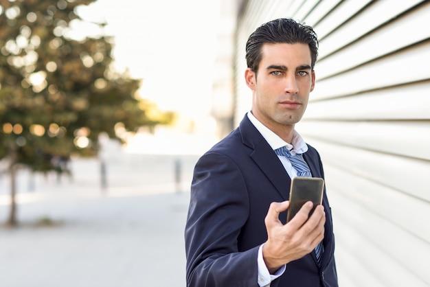 Ernstige zakenman met een gsm in de hand