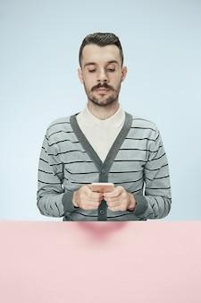 Ernstige zakenman met mobiele telefoon aan tafel zitten
