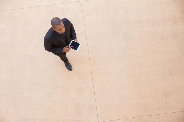 Ernstige zakenman met tablet die door bureauzaal gaat
