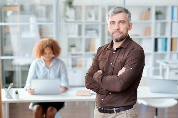 Ernstige zakenman met zijn armen gekruist op de borst staan voor de camera op de achtergrond van de werkende secretaris