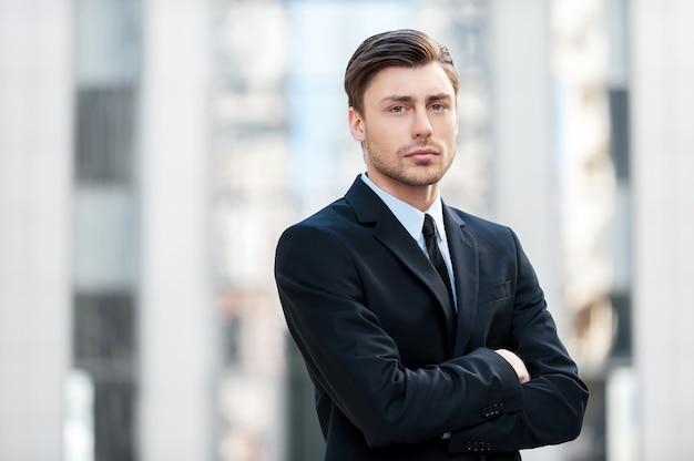 Ernstige zakenman. nadenkende jonge man in formalwear die de armen gekruist houdt en naar de camera kijkt