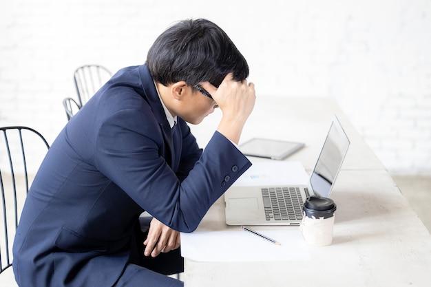 Ernstige zakenman op het werk, aziatische zakenman in stress zit formeel pak om serieus en hard te werken, ernstige zakenman die met computerlaptop werkt.
