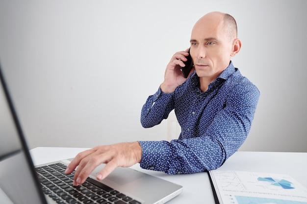 Ernstige zakenman van middelbare leeftijd die e-mails leest op het laptopscherm tijdens een telefoongesprek met zakenpartner of collega