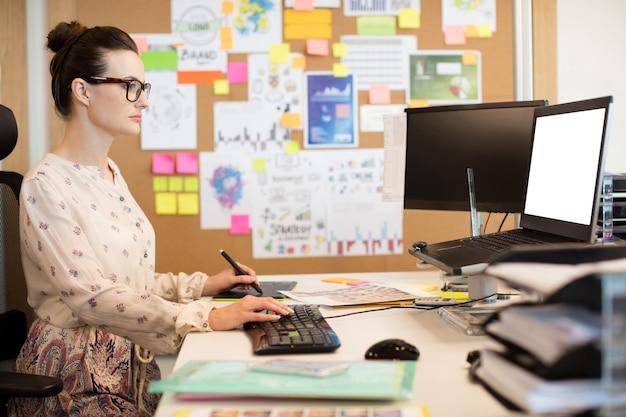 Ernstige zakenvrouw bezig met digitizer tijdens het gebruik van toetsenbord