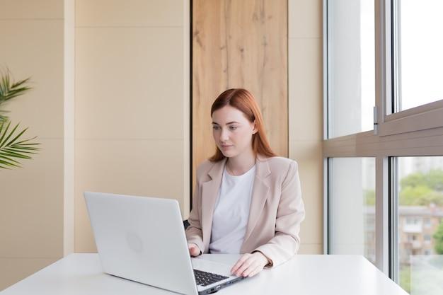 Ernstige zakenvrouw die aan een laptop werkt die aan een bureau zit