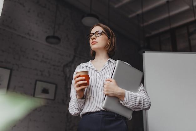 Ernstige zakenvrouw in stijlvolle blouse en zwarte broek met laptop en koffie drinken in kantoor.