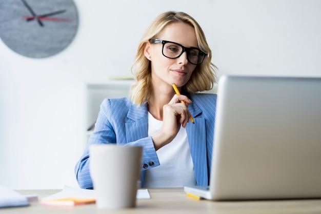 Ernstige zakenvrouw met behulp van laptop in heldere, moderne kantoren
