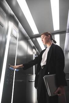 Ernstige zakenvrouw op de knop van de lift met smartphone in de ene hand
