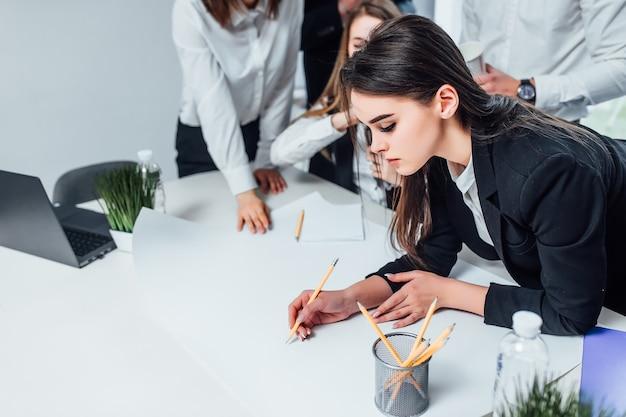 Ernstige zakenvrouw schilderen businessplan in modern kantoor met collega's.