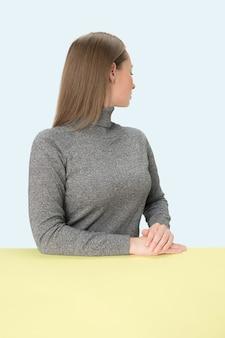 Ernstige zakenvrouw zitten weggedraaid aan tafel op een roze studio achtergrond.