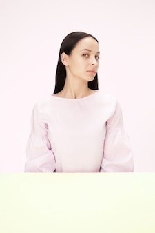 Ernstige zakenvrouw zittend aan tafel op een roze studio achtergrond. het portret in minimalistische stijl