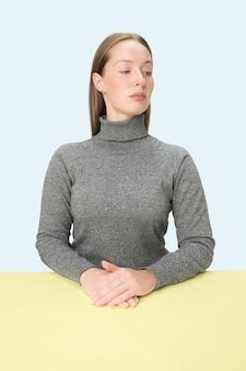 Ernstige zakenvrouw zittend aan tafel op een roze studio achtergrond.