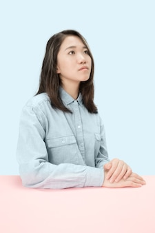 Ernstige zakenvrouw zittend aan tafel, opzoeken geïsoleerd op trendy blauwe studio achtergrond. vrouwelijke halve lengte portret.
