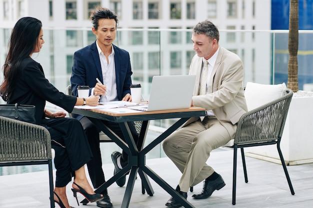 Ernstige zelfverzekerde bedrijfsmensen die financiële grafieken en rapporten bespreken en werk plannen tijdens de vergadering