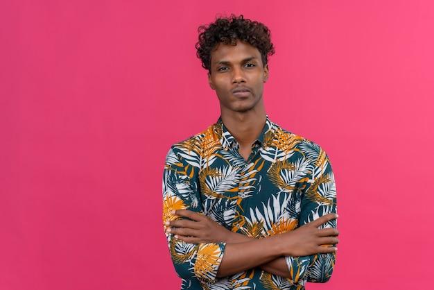 Ernstige zelfverzekerde donkere man met krullend haar in bladeren bedrukt overhemd hand in hand gevouwen terwijl hij naar de camera kijkt op een roze achtergrond