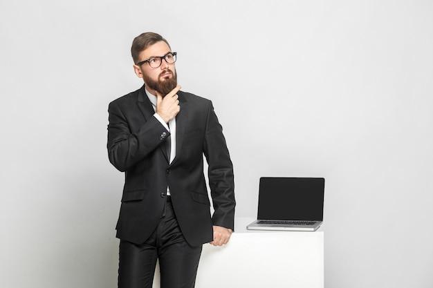 Ernstige zelfverzekerde doordachte bebaarde jonge zakenman in zwart pak staat in de buurt van zijn werkplek en houdt zijn baard vast met een geconcentreerd gezicht. geïsoleerd, studio-opname, binnen, grijze achtergrond